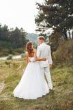 Beaux couples les épousant dans un domaine d'été images stock