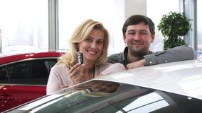 Beaux couples mûrs heureux posant près de leur nouvelle automobile tenant des clés de voiture banque de vidéos
