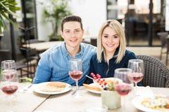 Beaux couples mangeant avec des amis Photographie stock libre de droits