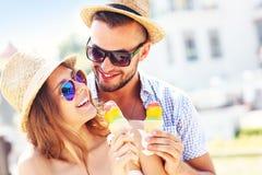 Beaux couples mangeant de la glace dans la ville Photographie stock libre de droits