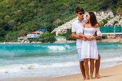 Beaux couples marchant sur une plage tropicale Photo stock