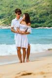 Beaux couples marchant sur une plage tropicale Photographie stock libre de droits