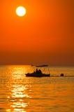 Beaux couples montant un bateau de pédale sur une mer au coucher du soleil dans Sithonia Photographie stock