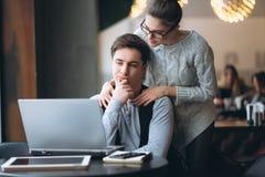 Beaux couples observant sur l'ordinateur portable dans le café Images stock