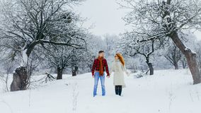 Beaux couples paisibles tenant des mains et marchant le long du chemin le long de la forêt d'hiver couverte de neige pelucheuse Images stock