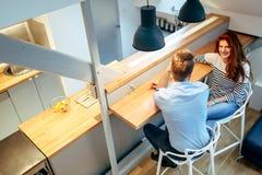 Beaux couples parlant dans leur maison immaculée Photo stock