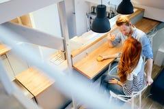 Beaux couples parlant dans leur maison immaculée Photos stock
