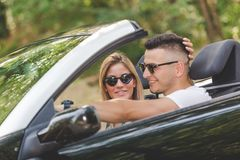 Beaux couples partant en vacances par l'entraînement dans la voiture de cabriolet en nature Images stock