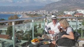 Beaux couples pluss âgé parlant sur la terrasse Jour ensoleillé Vue de mer Vers le haut du point clips vidéos