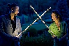 Beaux couples posant avec des épées de foudre Photographie stock
