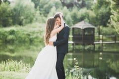 Beaux couples posant en parc Nouveaux mariés de lune de miel dans l'amour tenant des mains Photo stock