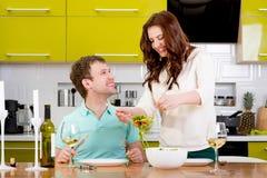 Beaux couples préparant au dîner avec de la salade et des pâtes Photos libres de droits