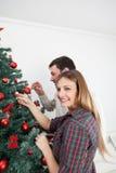 Beaux couples préparant l'arbre de Noël Images stock