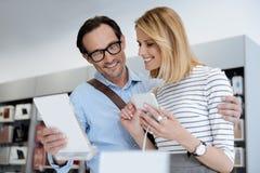 Beaux couples recherchant le nouveau smartphone au magasin Photos stock