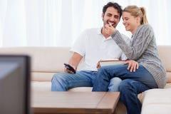 Beaux couples regardant la TV tout en mangeant du maïs éclaté Photo stock