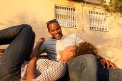 Beaux couples riants dehors sur le banc de parc image stock