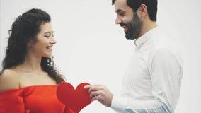 Beaux couples romantiques d'isolement sur le fond blanc Jeune femme attirante et étreinte belle de main avec le coeur rouge banque de vidéos