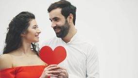Beaux couples romantiques d'isolement sur le fond blanc Une jeune femme attirante et un homme bel donne un coeur rouge banque de vidéos
