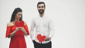 Beaux couples romantiques d'isolement sur le fond blanc Une jeune femme attirante et un homme bel tiennent les coeurs rouges deda clips vidéos