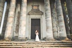 Beaux couples romantiques des jeunes mariés de nouveaux mariés étreignant près du vieux château Images stock