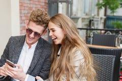 Beaux couples romantiques utilisant un nouveau téléphone sur le fond brouillé Concept de connexion internet Image stock