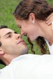 Beaux couples s'étendant dans l'herbe regardant dans chacun Images stock