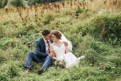 Beaux couples se reposant dans l'herbe sur le beau pré Photo stock