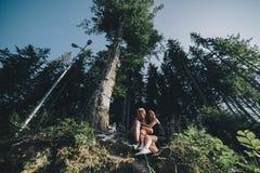 Beaux couples se reposant dans une forêt près de l'arbre Photos stock