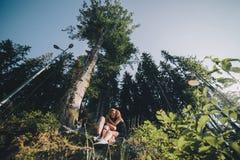 Beaux couples se reposant dans une forêt près de l'arbre Photographie stock
