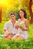 Beaux couples se reposant sur l'herbe dans le montant d'instagram de soirée photographie stock libre de droits