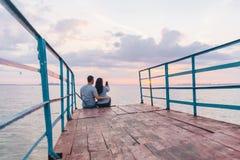 Beaux couples se reposant sur le pilier et regardant sur le lever de soleil Photos libres de droits