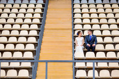 Beaux couples se reposant sur le support de stade de football Image stock