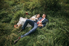 Beaux couples se situant dans l'herbe verte sur le pré Photo libre de droits
