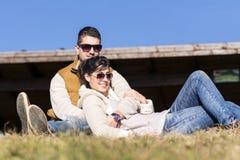 Beaux couples se trouvant et étreignant sur un pré Image libre de droits