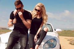 Beaux couples sexy dans des vêtements sport posant près de l'automobile photos libres de droits