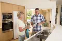 Beaux couples supérieurs de Moyen Âge environ 70 années à la maison de cuisine heureuse de sourire faisant la vaisselle semblant  Image stock