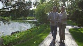 Beaux couples supérieurs marchant en parc d'été banque de vidéos