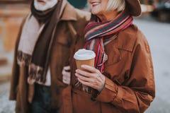 Beaux couples supérieurs marchant sur la rue et appréciant le café photos stock