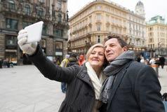 Beaux couples supérieurs sur une promenade au centre de la ville prenant le selfie Images stock
