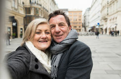 Beaux couples supérieurs sur une promenade au centre de la ville prenant le selfie Photo stock