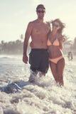 Beaux couples sur la plage ayant l'amusement Photos libres de droits