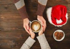 Beaux couples tenant la tasse de café dans des mains sur le fond en bois avec la vue supérieure de biscuits de chapeau et de choc Photos libres de droits