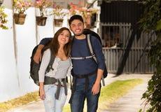 Beaux couples tenant les vêtements décontractés et les sacs à dos ensemble de port, posant pour l'attitude positive de sourire d' Images libres de droits
