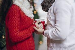 Beaux couples tenant une tasse de café dans la cour Photos stock