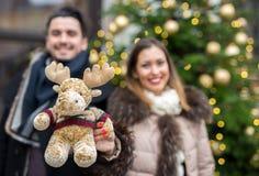 Beaux couples troubles donnant le jouet de renne pour Noël Photographie stock