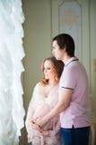 Beaux couples, une jeune femme enceinte et un homme, étreignant avec amour, dans l'intérieur de maison Images libres de droits