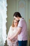 Beaux couples, une jeune femme enceinte et un homme, étreignant avec amour, dans l'intérieur de maison Images stock