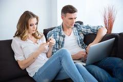 Beaux couples utilisant l'ordinateur portable et le smartphone séparément Image stock
