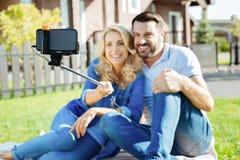 Beaux couples utilisant le bâton de selfie sur le pique-nique Photo stock