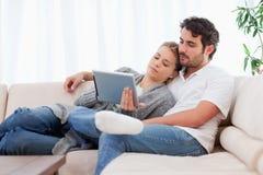 Beaux couples utilisant un ordinateur de tablette Photographie stock libre de droits